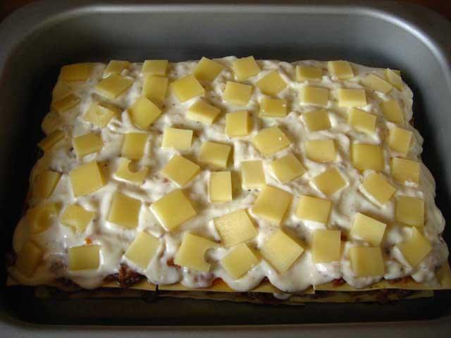 В другому шарі викладаємо порізаний сир на соус бешамель.