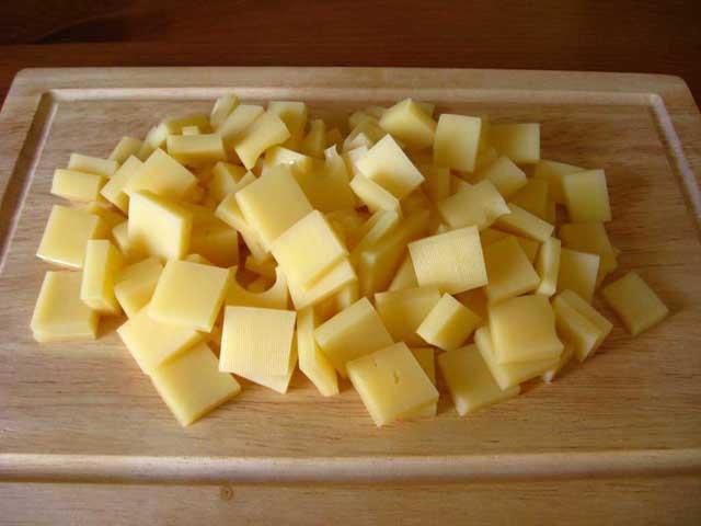 Нарізаний кубиками твердий сир.