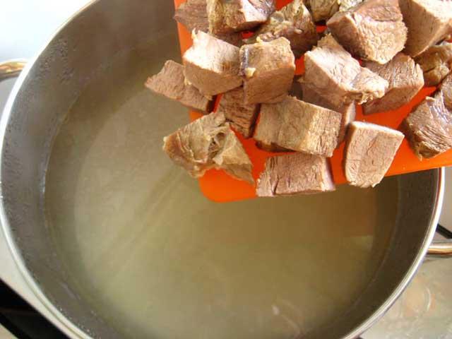 Додаємо нарізане м'ясо в каструлю.