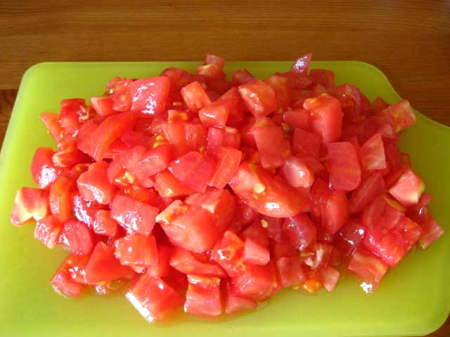 Нарізаний кубиками помідор.