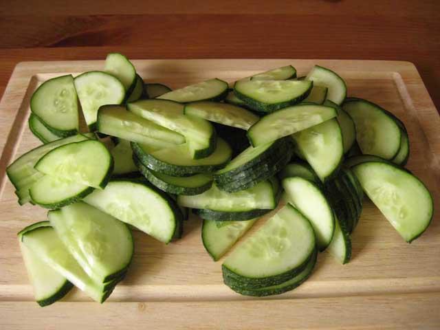Нарізані півкружельцями огірки.