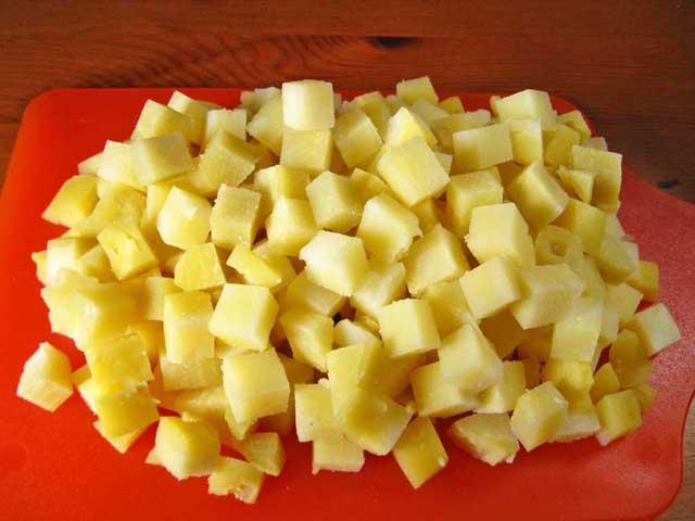Порізана кубиками картопля.