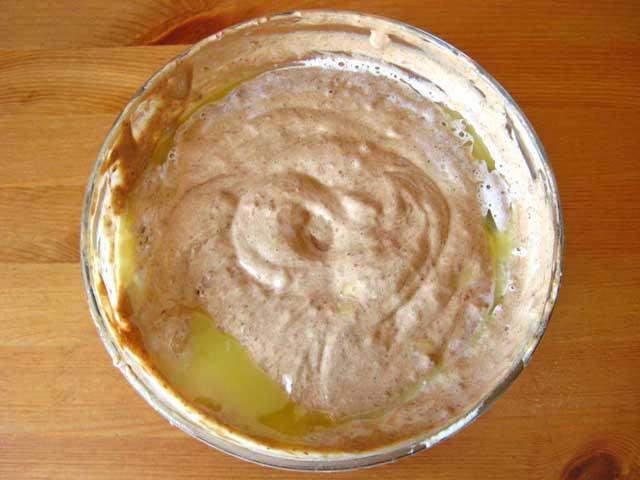 Додаємо борошно з какао до збитих яєць і вливаємо розтоплене на водяній бані масло. Розмішуємо.