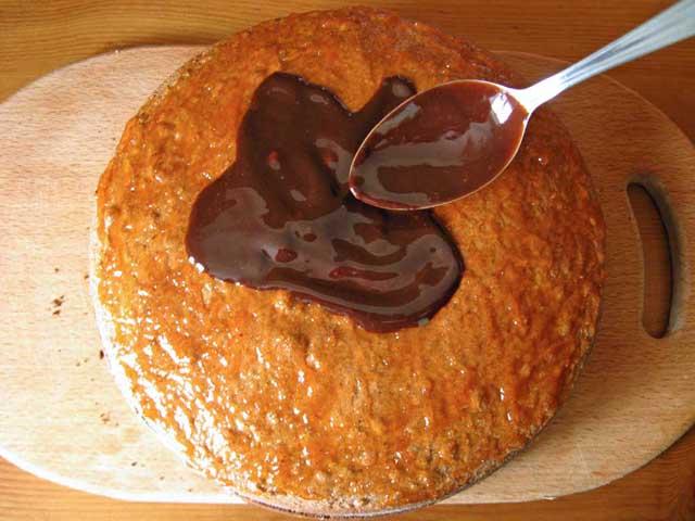 Зверху торт змащуємо джемом, даємо охолонути і поливаємо шоколадною помадкою.