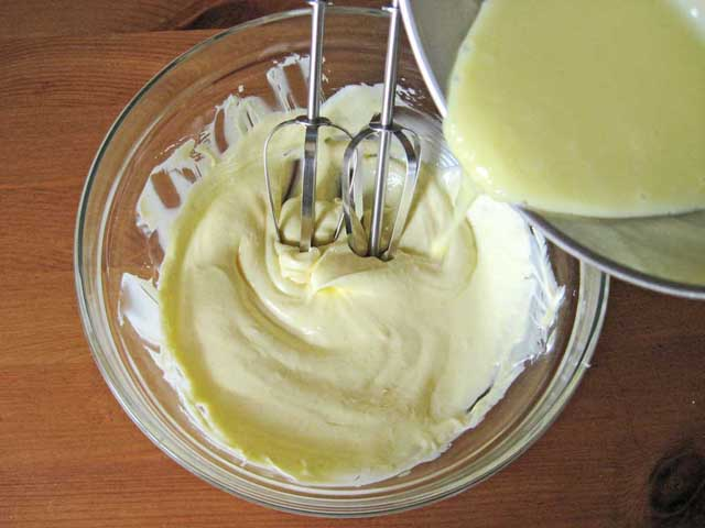 До масла додаємо жовток із згущеним молоком.